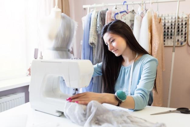 Het close-upportret van jonge indische naaister of naaister naait op naaimachine in haar eigen werkplaats.
