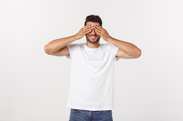 Het close-upportret van jonge kerel, mens, student, jongen, arbeider, werknemer, sluit ogen met handen, kan niet zien, verbergen, geïsoleerd op wit.