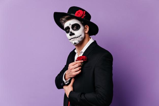 Het close-upportret van kerel in halloween-kostuum in mexicaanse stijl, die outfit met rode roos aanvult.