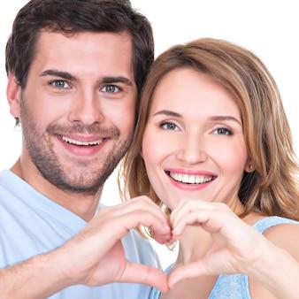 Het close-upportret van van vrolijk glimlachend paar die zich verenigen toont geïsoleerd handenhart -
