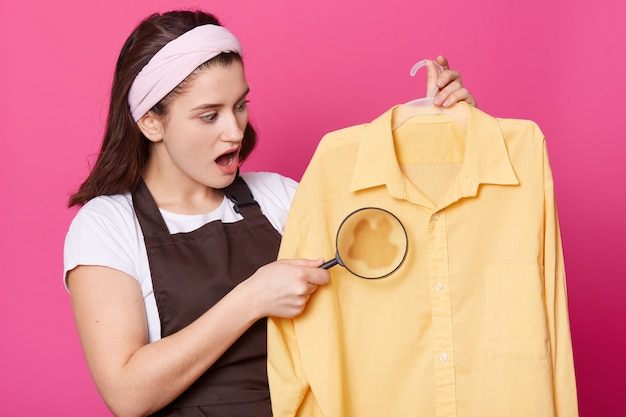 Het close-upportret van vrouw houdt meer magnifier en overhemd met in hand vlek. aantrekkelijke dame draagt wit overhemd en bruine schort ziet er verbaasd uit, staat met geopende ogen.