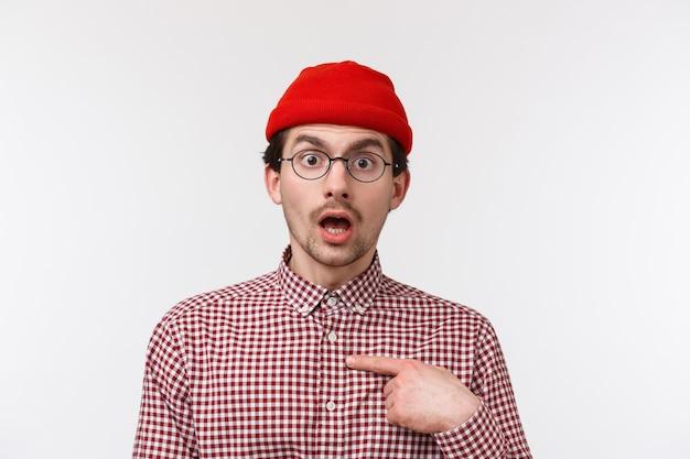 Het close-upportret verraste jonge hipsterkerel in glazen en beanie starend van ongeloof, wijzend besluiteloos, weet niet of de persoon hem echt noemde,