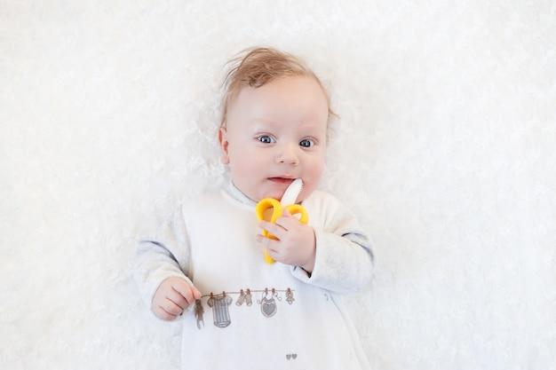 Het close-upportret weinig leuke jongen met grote blauwe ogen met een stuk speelgoed in zijn handen, knabbelt aan een stuk speelgoed van de banaanbijtring