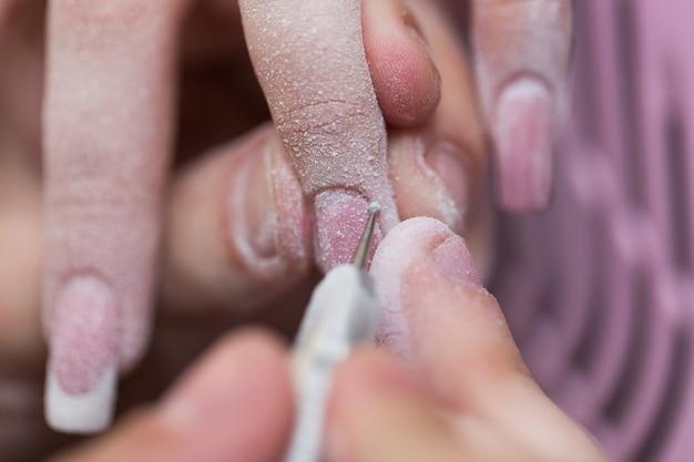Het close-upschot van meester gebruikt een elektrische machine om het nagellak tijdens manicure in de salon te verwijderen. hardware manicure. concept van lichaamsverzorging