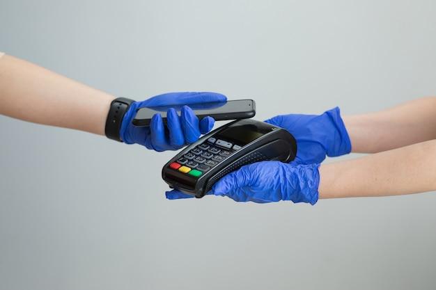 Het close-upschot van vrouw in handschoenen past smartphone toe op terminal die succesvolle contactloze betaling uitvoeren. klant die contactloos betaalt voor betalen via smartphone, nfc-technologie.