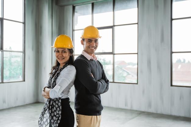 Het commerciële team rijtjes kruiste hun arm en droeg een bouwvakker