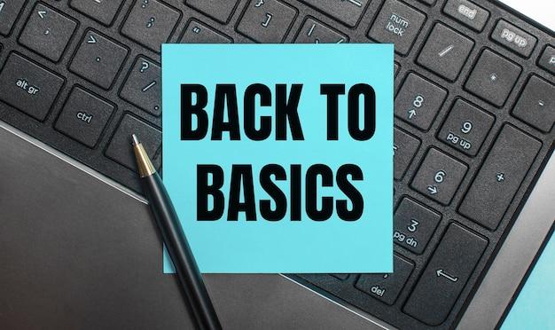 Het computertoetsenbord heeft een pen en een blauwe sticker met de tekst back to basics