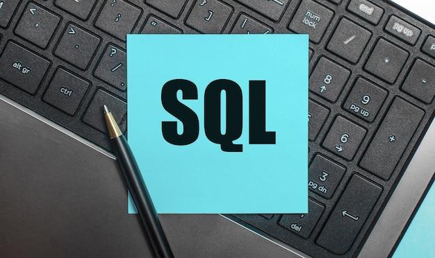 Het computertoetsenbord heeft een pen en een blauwe sticker met de tekst sql structured query language. plat leggen.