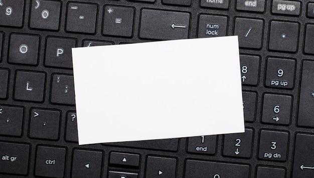 Het computertoetsenbord heeft een witte blanco kaart om tekst in te voegen. sjabloon. bovenaanzicht met kopie ruimte