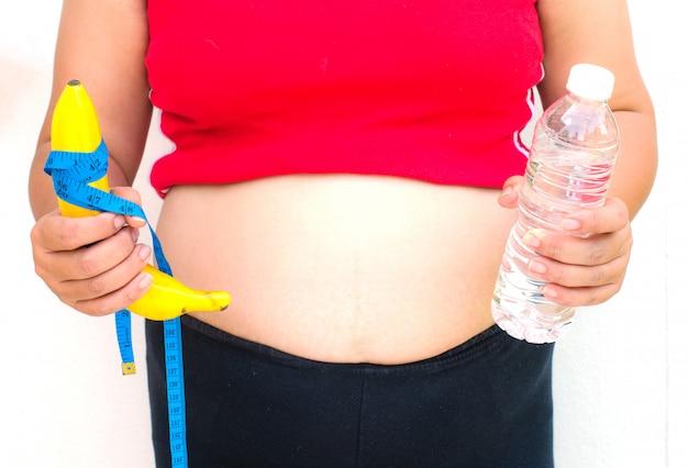 Het concept dieet voor gewichtsverlies - de vette vrouwen in hand hebben fruit en water.