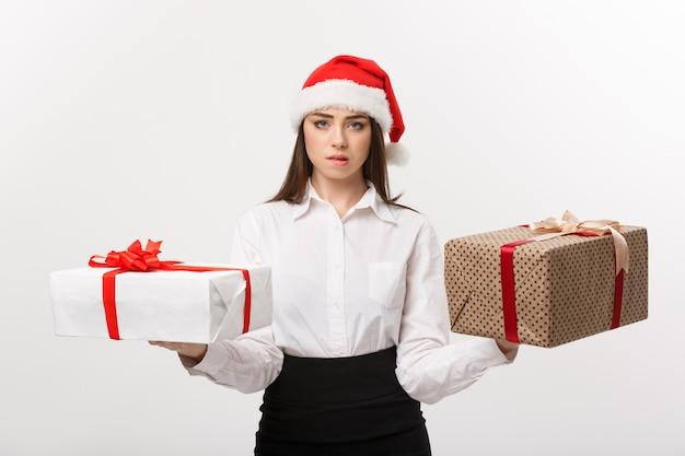 Het concept jonge gelukkige kaukasische bedrijfsvrouw van kerstmis die met santahoed giftdozen met exemplaarruimte aan kant kiezen