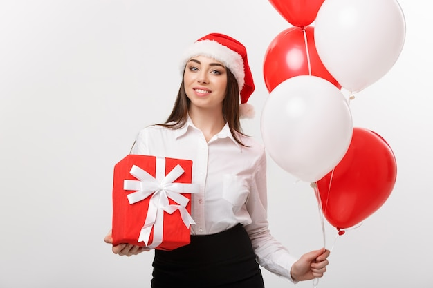 Het concept jonge gelukkige kaukasische bedrijfsvrouw van kerstmis met de doos van de de holdingsgift van de santahoed en ballon met exemplaarruimte aan kant
