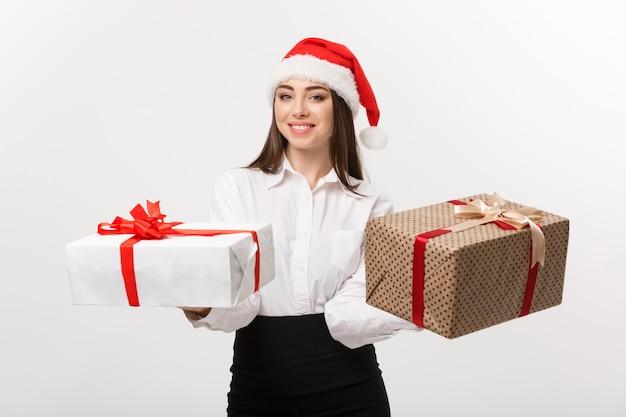 Het concept jonge gelukkige kaukasische bedrijfsvrouw van kerstmis met santahoed die een keus van giftdozen met exemplaarruimte aan kant geeft