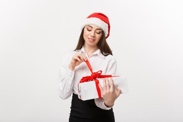 Het concept jonge gelukkige kaukasische bedrijfsvrouw van kerstmis met santahoed die terwijl open giftdoos met exemplaarruimte aan kant glimlachen
