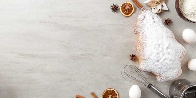 Het concept kerstkaart. zelfgemaakt bakken, ingrediënten, kerstboom-vormige koekjes en decoraties op een stenen achtergrond. bovenaanzicht, plat gelegd.