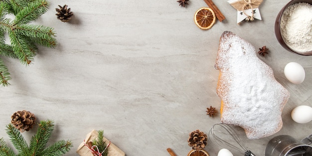 Het concept kerstkaart. zelfgemaakt bakken, ingrediënten, koekjes in de vorm van een kerstboom, geschenken, sparren takken en decoraties. bovenaanzicht, plat gelegd.