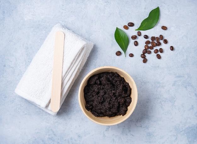 Het concept met natuurlijke ingrediënten voor de koffie van het huislichaam schrobt met koffiebonen en witte handdoek op blauwe achtergrond. verzorging van de huid van het lichaam. bovenaanzicht en kopie ruimte