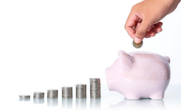 Het concept om geld te besparen, hand die een muntstuk zet in spaarvarken op wit