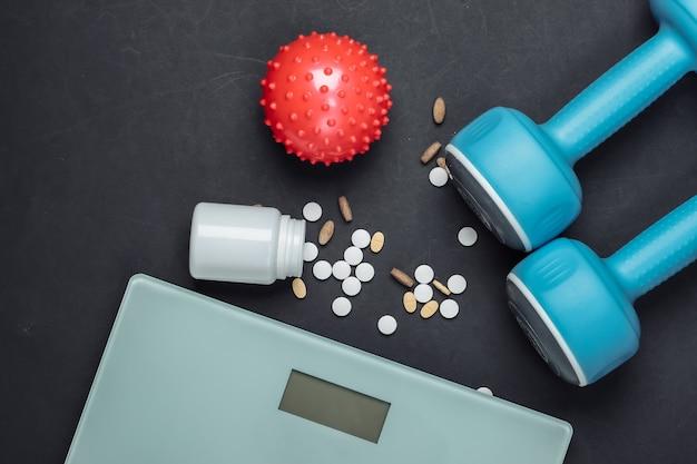 Het concept van afvallen. halters, pillen, vloerweegschalen voor massagebal