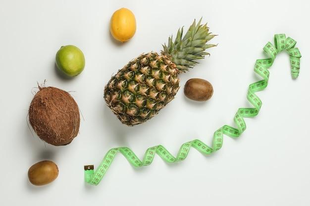 Het concept van afvallen. tropische vruchten en meetlint op een witte achtergrond. gezond eten. fruit dieet. bovenaanzicht