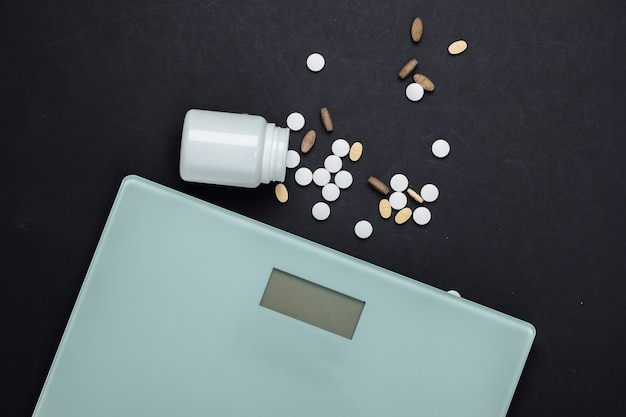 Het concept van afvallen. vloerweegschaal, een fles pillenvitaminen op zwart.