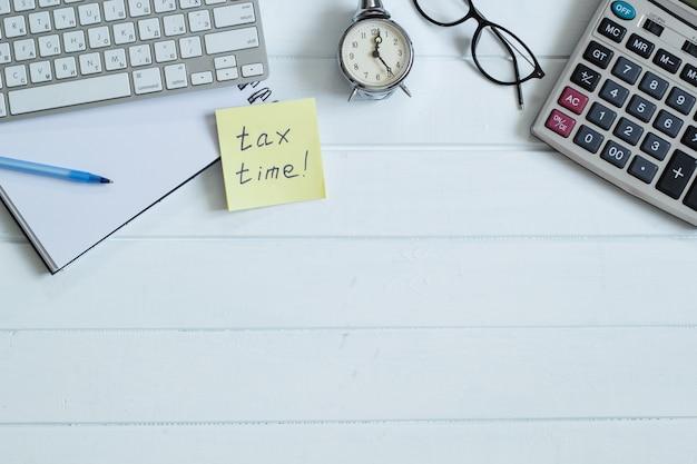 Het concept van belastingtijd. desktop zoncalculator en glazen. ruimte kopiëren. bovenaanzicht.