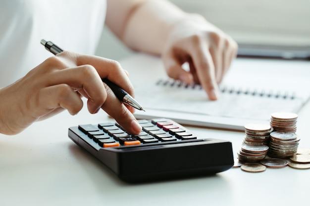 Het concept van de belasting. de vrouwenhand gebruikend calculator en het schrijven maken nota met berekenen over kosten thuis kantoor. werk vanuit huis