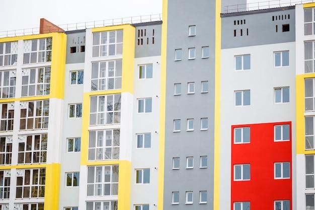 Het concept van de bouw van gebouwen met meerdere verdiepingen. bouwisolatie en geveldecoratie. kunststof ramen in huis. onvoltooide constructie