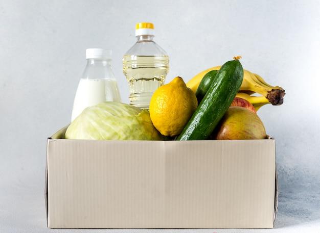Het concept van de de doosdonatie van de voedsellevering de donatieconcept. donatiebox met groenten, fruit en ander voedsel voor mensen