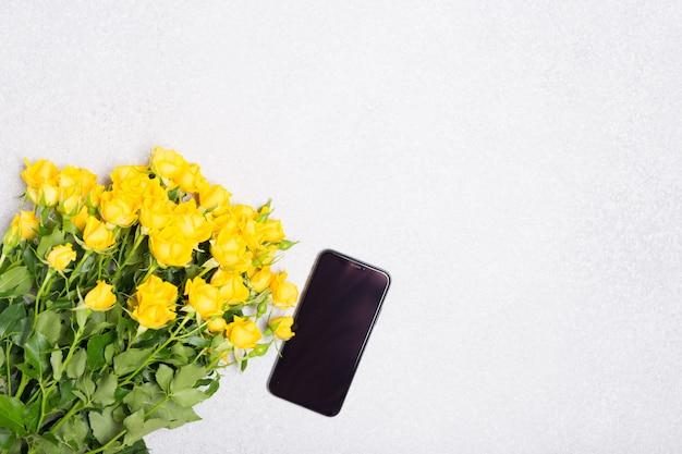 Het concept van de de lentezomer met gele rozenbloemen en telefoon op witte lijstachtergrond
