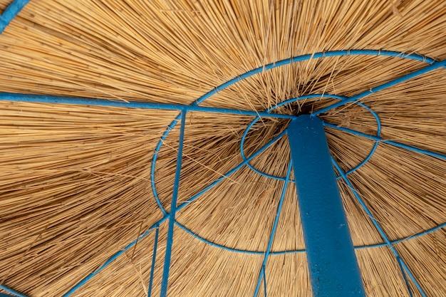 Het concept van de de zomervakantie met een deel van een parasol van riet, blauwe steun wordt gemaakt die