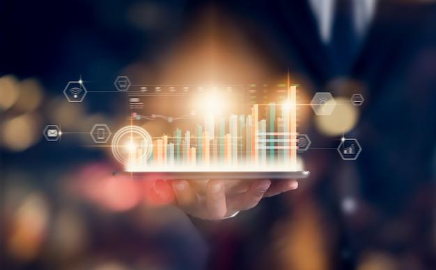 Het concept van de effectenbeursmarkt, de tablet van de handhandelaar met de kaarslijn van de grafiekenanalyse op bokeh kleurt licht in nacht.