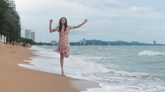 Het concept van de het strandvakantie van de zomer, gelukkige jonge aziatische vrouw