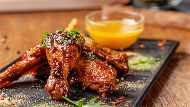 Het concept van de indiase keuken. gebakken kippenvleugels en poten in honing-mosterdsaus. dienende schotels in het restaurant op een zwarte plaat. indiase kruiden op een houten tafel. achtergrond afbeelding.