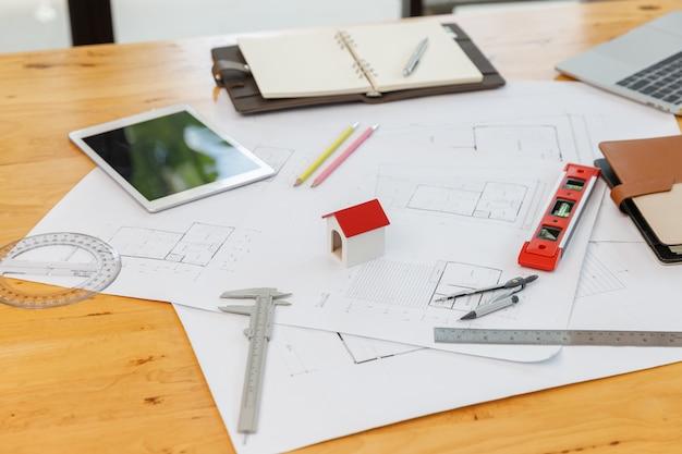 Het concept van de ingenieur en van de architect, sluit huismodel op het bureau van de binnenlandse ontwerper met blauwdruk