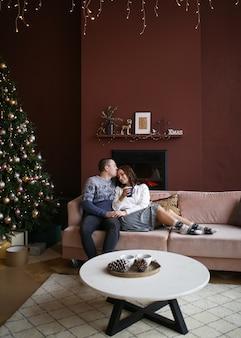 Het concept van de kerstopnames, het gelukkige paar vierde de vakantie thuis bij de open haard