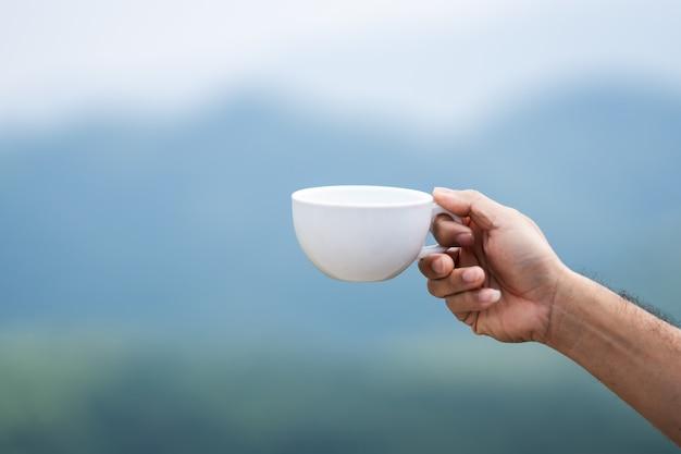 Het concept van de koffieaard, koffiekop op handholding op aard van mist op berg en hemel