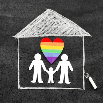 Het concept van de krijtfamilie dat op bord met een regenbooghart wordt getrokken