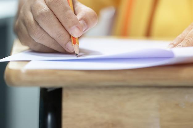Het concept van de onderwijstest: man hands-middelbare school, het universitaire potlood van de studentenholding voor het testen