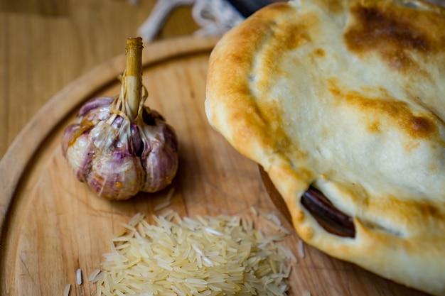 Het concept van de oosterse keuken. zelfgemaakte georgische oezbeekse pilaf of plov van lam geserveerd in gietijzeren kookgerei.