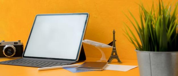 Het concept van de reisvoorbereiding met lege het schermtablet, camera, paspoort en decoratie op gele achtergrond
