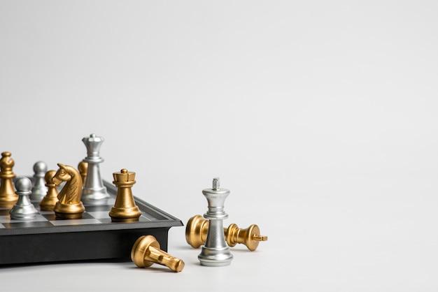 Het concept van de schaakleiding met gouden en zilveren die schaak op witte achtergrond wordt geïsoleerd.