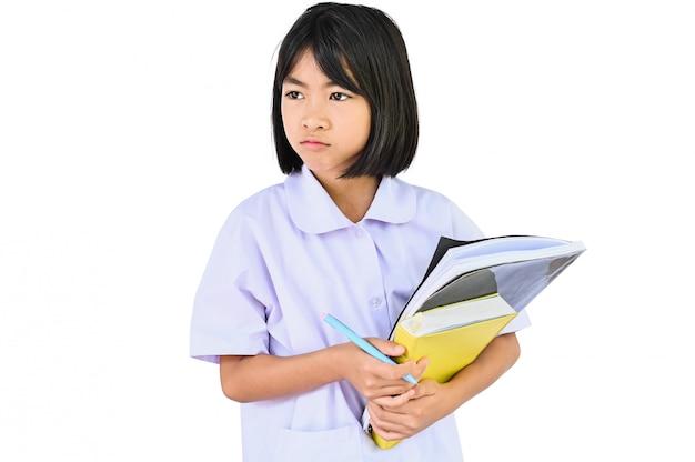Het concept van de thuisschool, aziatische kinderen die stapelboeken houden, bekijkt hen vragend en wil niet studeren