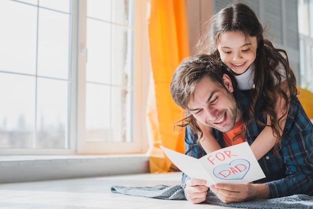Het concept van de vadersdag met vader die ter beschikking getrokken kaart lezen