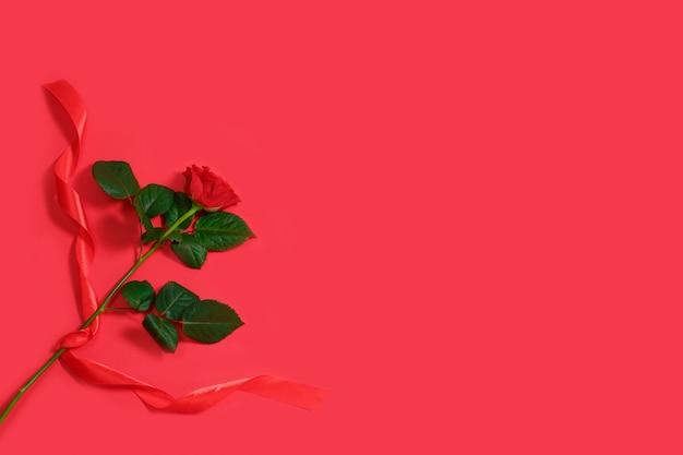 Het concept van de valentijnskaartendag met rood nam en lint op rode achtergrond toe.