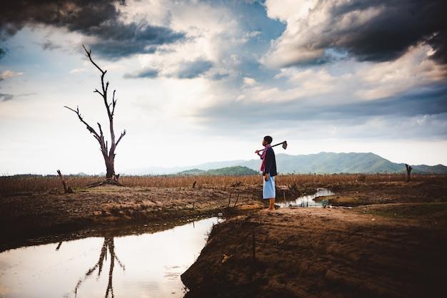 Het concept van de watercrisis, hopeloze en eenzame landbouwer zit op gebarsten aarde dichtbij droogend water.