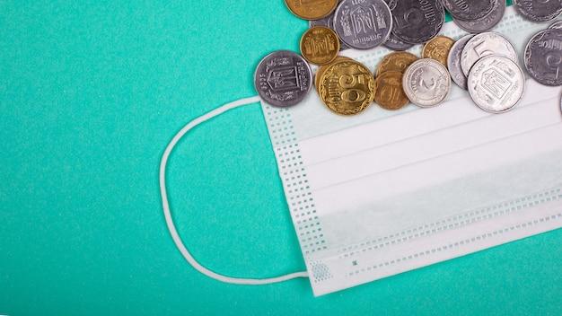 Het concept van de wereldwijde medische crisis in verband met de coronavirus pandemie. beschermend medisch masker en munten op een blauwgroene achtergrond.