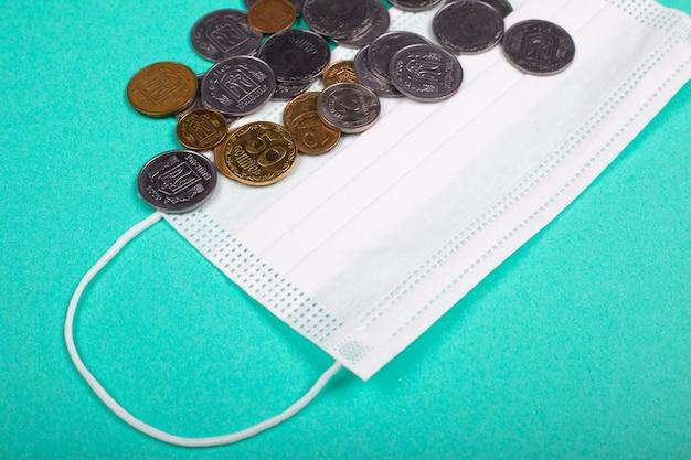 Het concept van de wereldwijde medische crisis in verband met de coronavirus pandemie. beschermend medisch masker en munten.