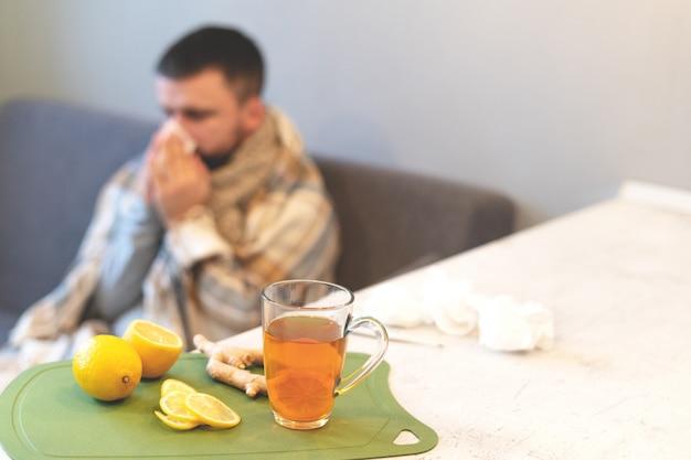 Het concept van de ziekte, wintertijd. zwarte thee, citroen en gember op de tafel, een zieke man, griep. epidemie, ziekteverzuim, temperatuur, stress