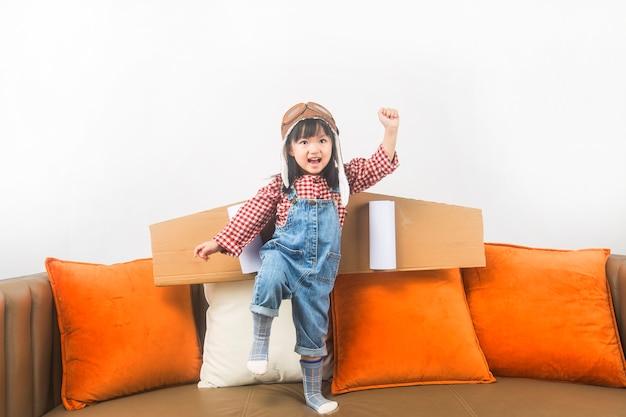 Het concept van dromen en reizen. het kind speelt de rol van een piloot en droomt ervan de ruimte in te vliegen.